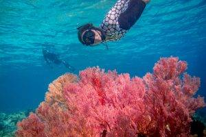 woman wearing an ocean mimic suit snorkelling with coral