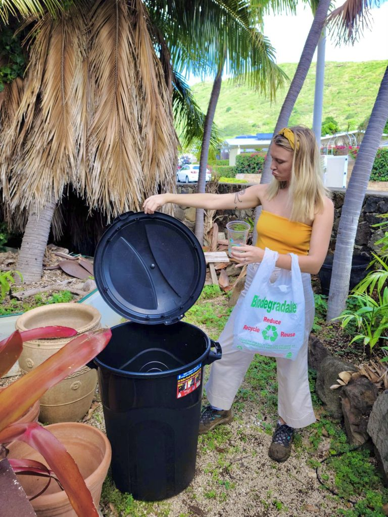 girl holding bioplastic products next to a bin