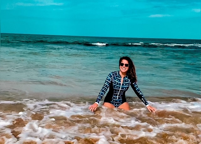 Melissa wearing the ocean mimic whale shark suit in the surf on a beach