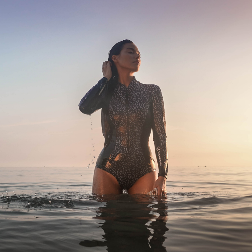 woman wearing a black and white spotted eagle ray design body suit in the ocean